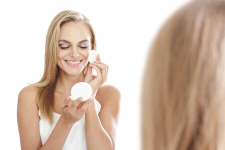 schöne augen: Porträt der schönen blonden Frau, die Anwendung Pulver mit geschlossenen Augen auf weißem Hintergrund