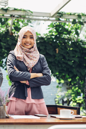 asian lifestyle: portrait of confident muslim asian businesswoman with armcrossed smiling to camera