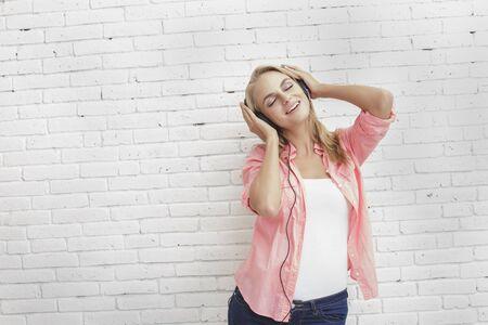 listening to music: retrato de la chica rubia ocasional gusta escuchar la música que usa los auriculares con copia espacio sobre fondo blanco pared de ladrillo