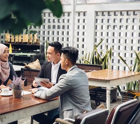 ビジネスマンやビジネスウーマンのカフェでタブレット pc コンピューター会議で笑みを浮かべてビジネス人々 の技術とチームワーク コンセプト