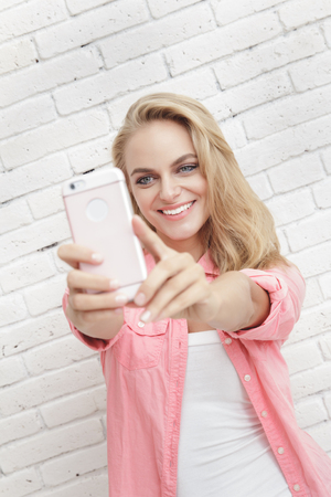 mobilephone: portrait of beautiful woman smiling while taking photo using mobilephone camera Stock Photo