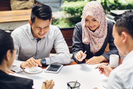 Portret van jonge Aziatische mensen uit het bedrijfsleven bijeen in een cafe