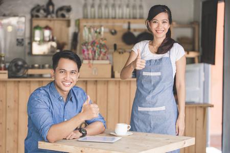 幸せな顧客と親指を現して女性ウェイターの肖像画 写真素材