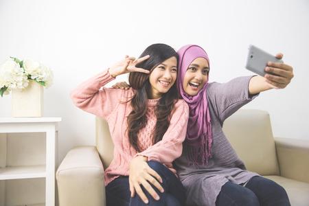 Dos felices joven musulmana tomar autorretrato con el teléfono inteligente en el hogar Foto de archivo - 57127237