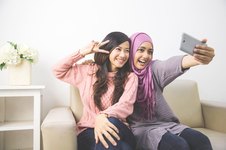 two happy young muslim woman take self portrait with handphone at home Stock Photo
