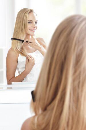 cabello rubio: retrato de la hermosa mujer rubia con el pelo largo poner en orden su pelo usando el peine del pelo