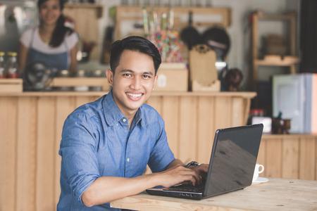 카페에서 랩톱을 사용하는 잘 생긴 아시아 웃는 남자의 초상화