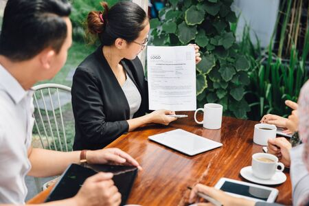 colleagues: portrait of young asian businesswoman doing presentation while meeting in a cafe Stock Photo