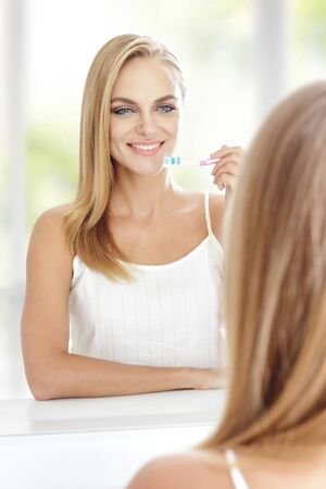 hair brush: portrait of beautiful blonde woman holding tooth brush