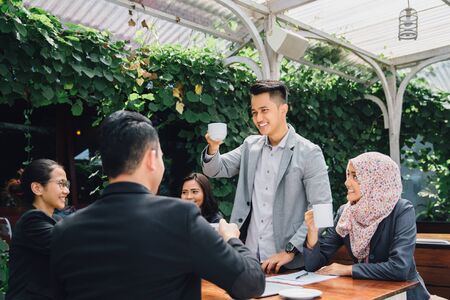 muslim celebration: happy asian business Friends Cheering With Coffee at cafe