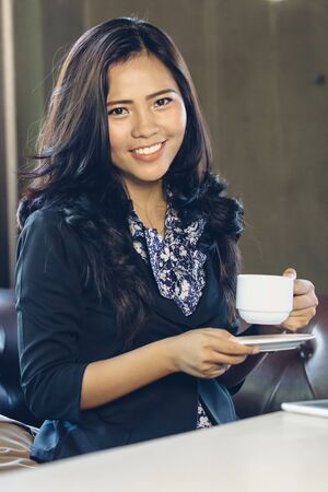 asian businesswoman: Young businesswoman on a coffee break smiling to camera