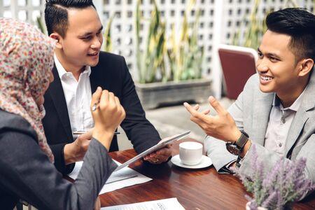 usando computadora: retrato de gente de negocios reunidos en un café