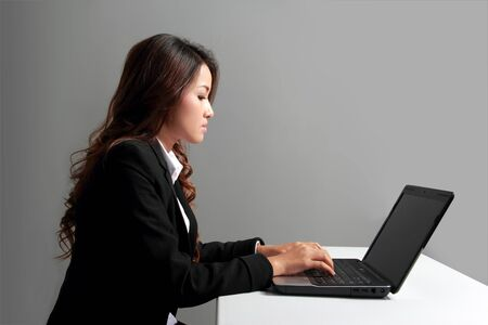 asian businesswoman: Portrait of business woman working with laptop on the table from side angle