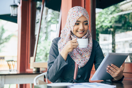 Joven empresaria en un descanso para tomar café. Usando la tableta Foto de archivo - 57127792