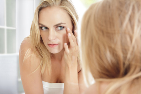 wash face: portrait of beautiful young woman looking into the mirror and touching her smooth face Stock Photo