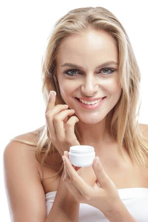 young add: portrait of beautiful blonde woman applying some facial cream on her cheek isolated on white background Stock Photo