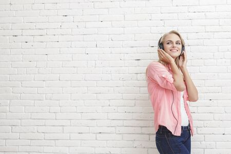 asian lifestyle: portrait of happy young girl listening music wearing headphones with copy space