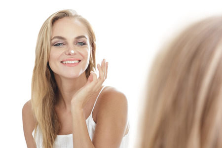 young add: portrait of beautiful blonde woman applying some facial cream on her nose isolated on white background