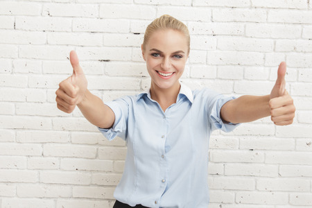 two thumbs up: portrait of beautiful businesswoman smiling and giving two thumbs up