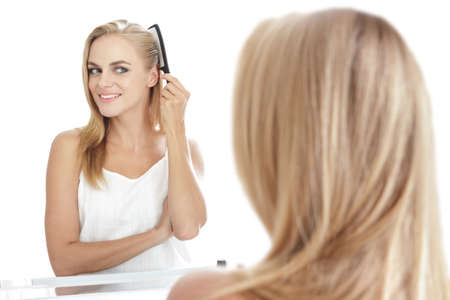 comb hair: portrait of beautiful blonde woman with long hair tidy up her hair using hair comb Stock Photo