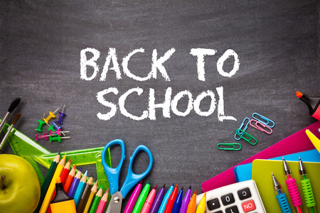 School supplies on blackboard background. back to school concept Stock Photo