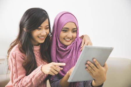 Deux jolies femmes asiatiques en utilisant la tablette ensemble à la maison