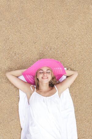 summer holidays: portrait of beautiful lying down relaxing on the sand on during summer holidays with copy space