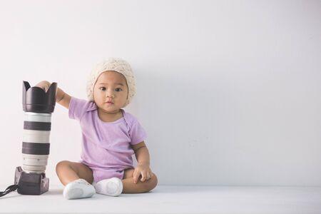 petit photographe de bébé assis sur la tenue appareil photo reflex numérique de plancher Banque d'images