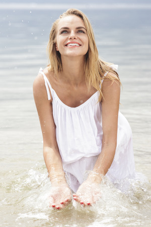 young woman smiling: portrait of cheerful woman playing water on the beach during summer holidays Stock Photo
