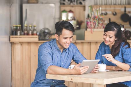 Ritratto di due giovani business partner utilizzando tablet insieme al caffè
