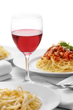 spaghetti: portrait of red wine on glass with italian pasta cuisine isolated on white background