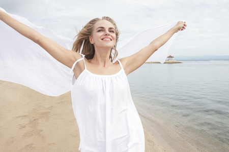 feeling happy: portrait of young woman feeling happy with white scarf on the beach Stock Photo