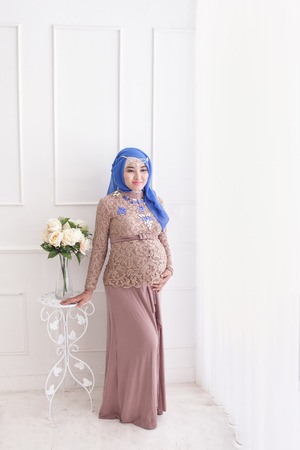 womb: full body portrait of an asian pregnant woman wearing hijab