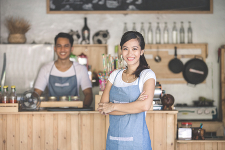 Successful small business owner standing with crossed arms with partner at the background Stok Fotoğraf
