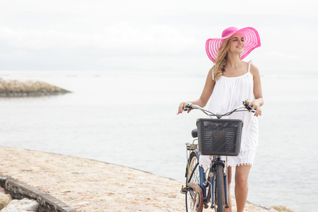 young woman smiling: portrait of young woman wearing pink sunhat walking with bicycle on the beach with copy space Stock Photo
