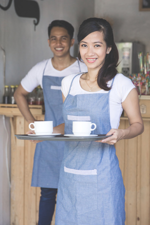 business asia: portrait of young female waitress serving coffe at the cafe Stock Photo