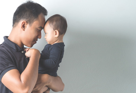 adult baby: A portrait of a Young Asian father holding his adorable baby on white background