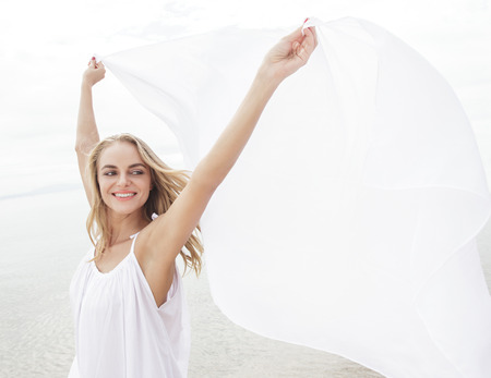 scarf beach: portrait of happiness of beautiful woman with white scarf on the beach Stock Photo