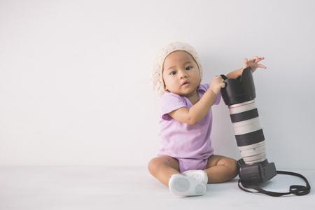 dslr: little baby photographer sitting on the floor holding dslr camera