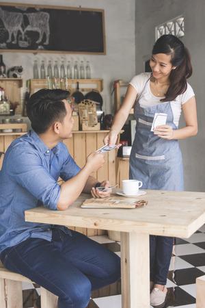 笑顔のお客様コーヒー ショップで現金で支払い