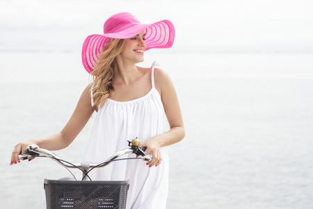 sunhat: portrait of young woman wearing pink sunhat walking with bicycle along beach with copy space