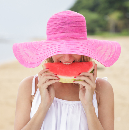 close up portrait of young woman wearing pink sunhat eating fresh watermelon on the beach