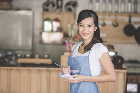 Happy attractive asian female waiter in apron writing order and looking at camera