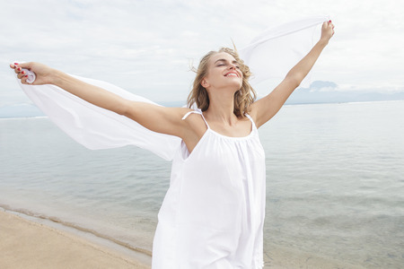 scarf beach: portrait of beautiful young woman feeling happy with white scarf on the beach Stock Photo