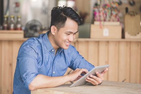 Immagine di giovane uomo felice con tavoletta digitale nel caffè