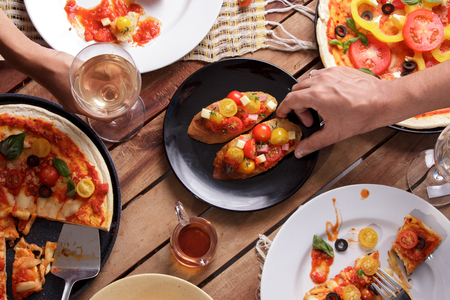 portrait of some italian cuisine on wooden table with human hands
