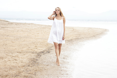 beautiful woman body: full body portrait of beautiful woman walking on the beach enjoying summer Stock Photo