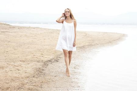 mujer cuerpo completo: Retrato de cuerpo entero de la mujer hermosa que recorre en la playa disfrutando del verano Foto de archivo