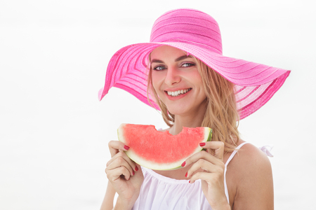 sunhat: portrait of beautiful woman wearing pink sunhat smiling and eating watermelon isolated on white background