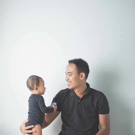 girl bonding: A portrait of a Young Asian father holding his adorable baby on white background